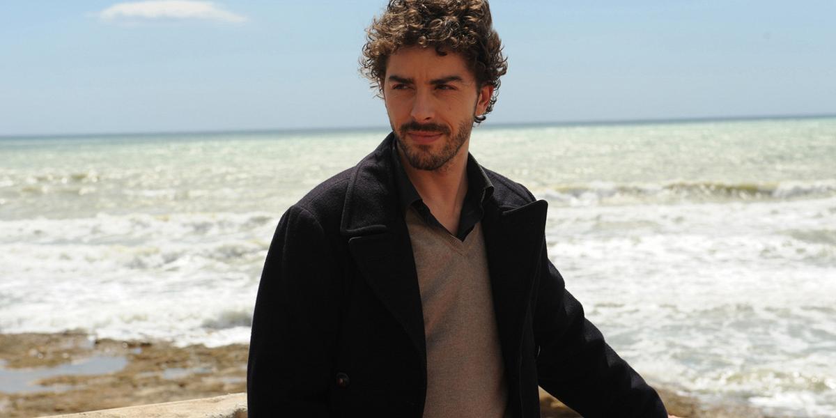 Com'è oggi l'attore Michele Riondino, ex attore di Distretto di Polizia. Lo vediamo in piedi, pensieroso, in riva al mare.